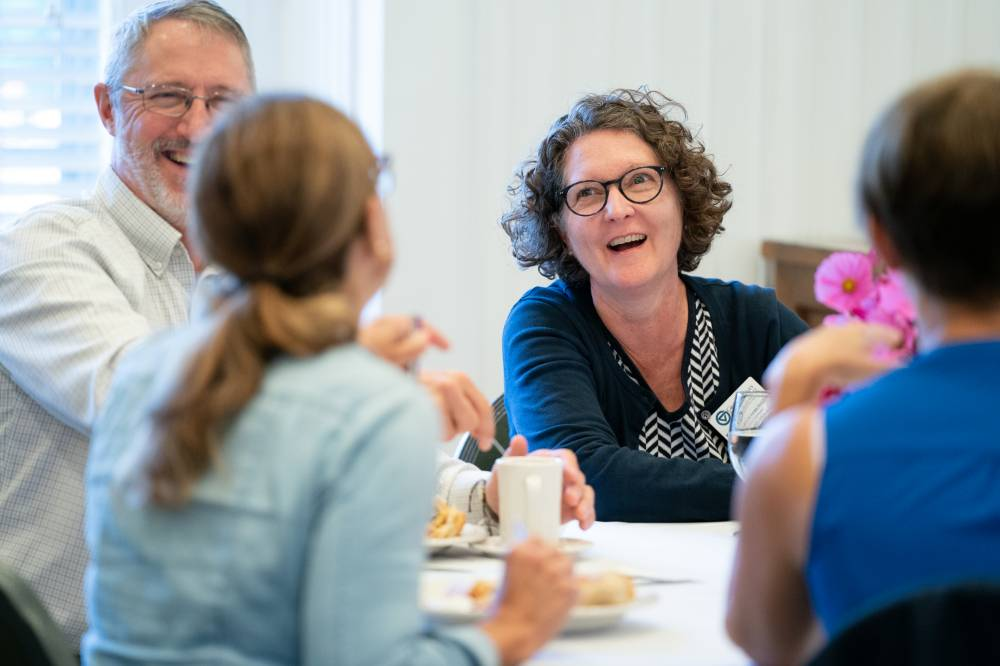 Faculty members laugh together at a table